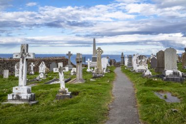 LLANDUDNO , WALES, UK - APRIL 22 2018 : Dramtic graves standing at St Tudnos church and cemetery on the Great Orme at Llandudno, Wales, UK. stock vector