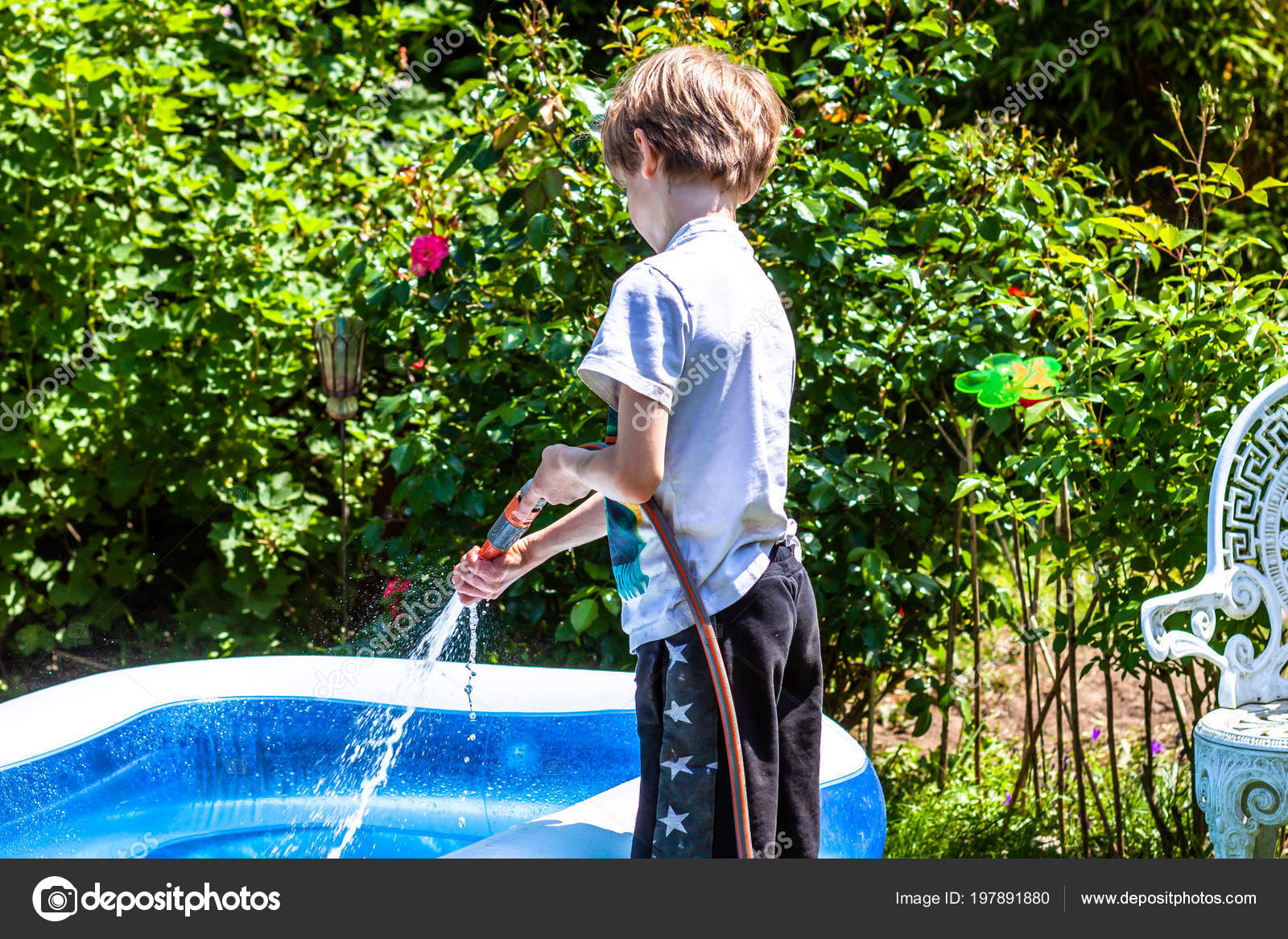 Little boy filling filling swimming pool with water — Stock ...