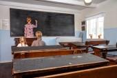 Nyilvános általános iskolai oktatás, a fiatal fiú és lány hallgatja a tanárnőt fogalmának