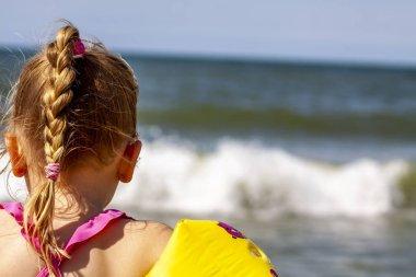 Happy little girl with floaties floaties preparing to swim in the ocean