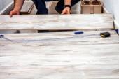 Muž instalace nové dřevěné laminátové podlahy doma.