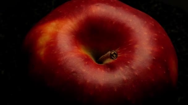 Red apple on dark background moving on a turntable