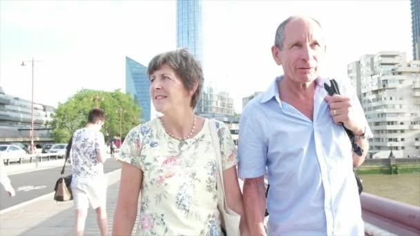 Lassú mozgás folyamatos kamera nézet aktív vezető kaukázusi turista házaspár séta a blackfriars bridge london, a Temze mögött