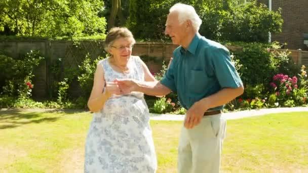 Aktivní Senior bezstarostné Kavkazský pár jive tančí v jejich zahradě