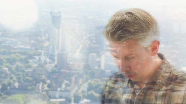 Muž v neformálním oblečení při pohledu na jeho smartphone proti sklo panorama za