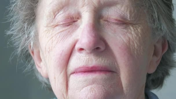 Portrait of a senior caucasian woman opening her eyes