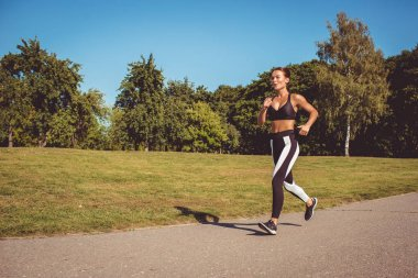 beautiful woman in black white leggings and sportive top running in park