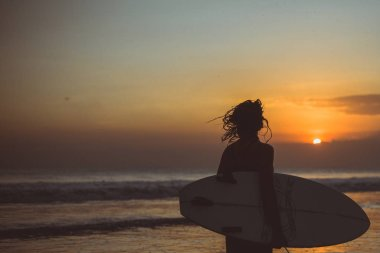 woman silhouette with surfboard in sea at sunset