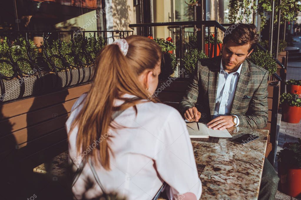 handsome Caucasian man sitting outdoors in cafe at meeting with woman