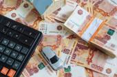 Koncepce nákupu nemovitostí a automobilu: uspořádání domu, psacího stroje, kalkulačky a hromádky ruských rubů v bankovním balíčku, který leží na pozadí roztroušených bankovek
