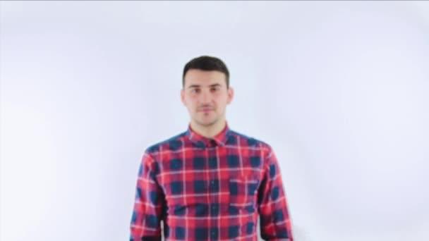 Pohledný mladík s oblečením červená košile chůze do kamery se zkříženýma rukama nad bílým pozadím.