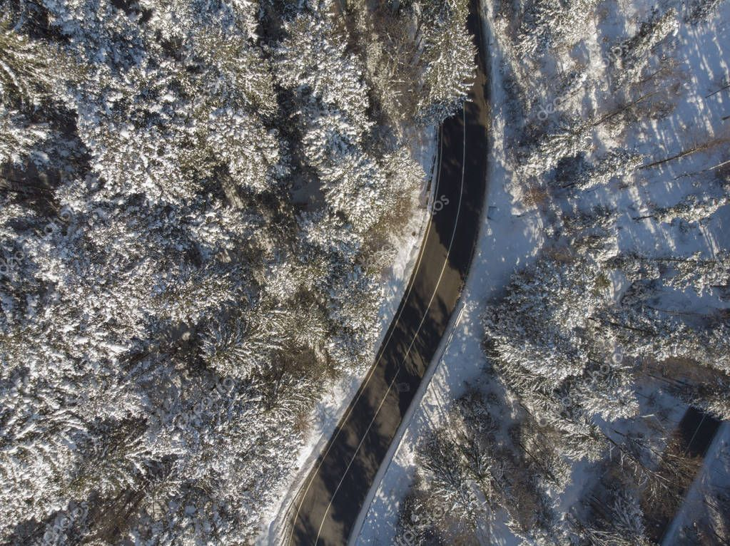 straight road in winter mountain landscape. Aerial view of forest