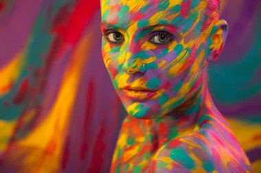 Portrait of the bright beautiful woman with art colorful make-up and bodyart