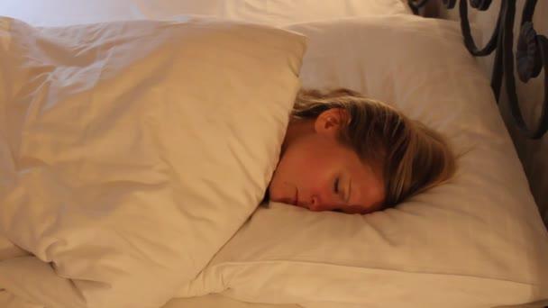 Fiatal nő alszik az ágyban, rossz álmodik, a változó helyzetben