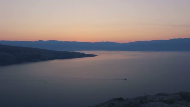 Kleines Boot schwimmt im Sonnenaufgang auf dem Meer
