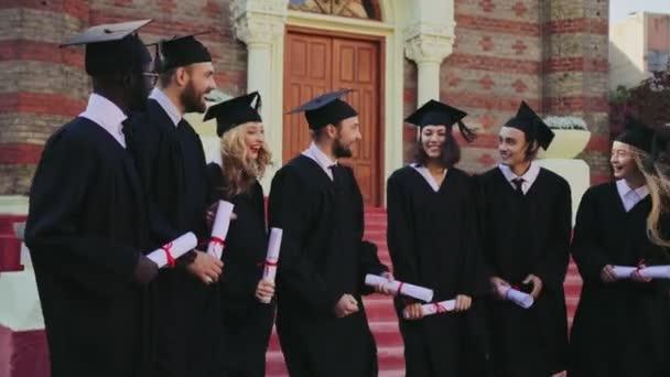 Kevert emberfajták meg a diplomások állandó az egyetemen, és boldog a különleges ruhák és sapkák. A szabadban