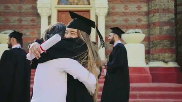 Gray-haired father congratulating his pretty blonde daughter with getting a diploma on the graduation day near the University entrance. Outside