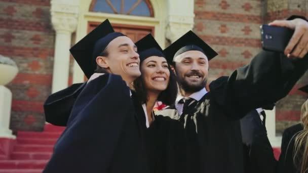 Portrét shot šťastný absolventů, takže selfie na černý smartphone vodorovně poblíž univerzitní budovy. Venkovní