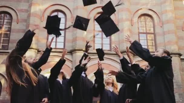 Skupina více etnických absolventů v tradiční oblečení vyhazoval jejich čepice ve vzduchu šťastně před univerzitou. Venku