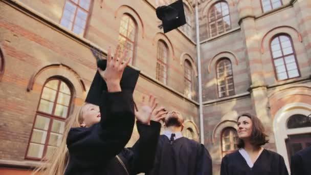 Mladí multi etnických absolventů stát v jedné řadě a vymrštilo čepicích promoce ve vzduchu jeden po druhém na nádvoří univerzity. Vně
