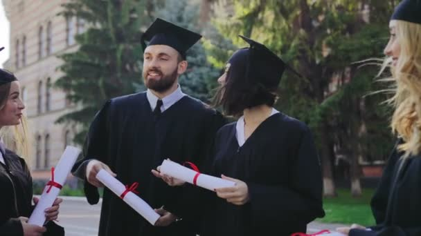 Group of mixed races male and female graduates in traditional clothes and caps with diplomas in hands talking and laughing. Outdoors
