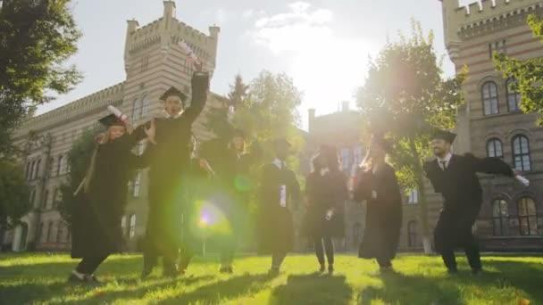Skupina multi etnické absolventů, vyskočil v tradičním oblečení a čepice a diplomy v rukou na den šťastnou maturitu. Venku