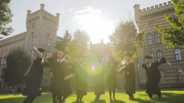 Skupina Smíšené rasy absolventů, vyskočil v tradiční šaty a čepice a diplomy v rukou na slunném závěrečný den. Vně