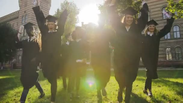 Více etnických absolventů v černé šaty a čepice vesele běží s jejich diplomů v ruce před jejich univerzity za slunečného dne. Venkovní