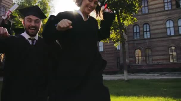 Mixed races friends in graduation black gowns and caps running happily and joyfully from their University on a sunny day. Outside