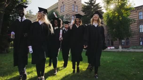 Mnohonárodnostní mužských a ženských absolventů v tradiční černé šaty a čepice vesele chodí a mluví s jejich diplomů v rukou od budovy univerzity. Venku