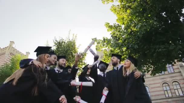 Více etnických absolventi baví a zvracel jejich diplomů po promoci před budovou univerzity. Venkovní