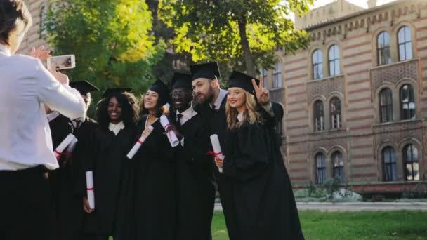 Zadní část šedovlasý muž s fotografii na smartphone skupiny Smíšené rasy absolventů v tradiční černé šaty a čepice s diplomy v rukou. Venkovní