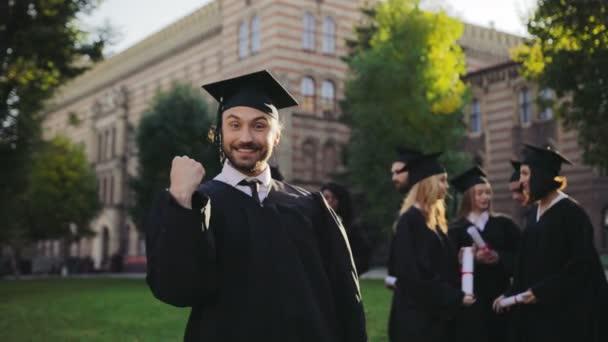 Portrét shot šťastný veselý a zábavný muž v tradiční Maturitní šaty a čepice s diplomem v rukou baví a šklebící se do kamery. Absolventi na pozadí. Venku