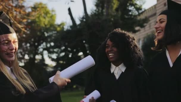 Zblízka ženské absolventů v černé šaty a čepice pro zábavu a smích v parku jejich univerzitní budovy. Venku