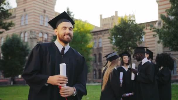 Portré a vonzó fiatal diplomás ember fekete hagyományos ruhákat és kap pózol a kamerába, és mosolyog. Diplomások a háttérben. Kültéri