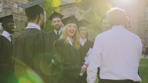 Middle aged man coming to the group of graduates in black gowns and caps and congratulating them with getting diplomas after the ceremony. Outdoors