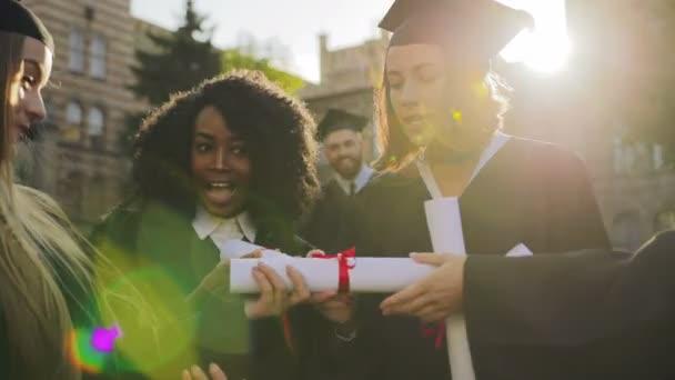 Okouzlující mladá žena absolventů v tradiční šaty a čepice rozvinutím diplom a řekl: Wow, při pohledu na něj. Kluci na pozadí. Vně