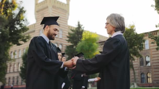 Middle aged professor congratulating attractive graduated man and giving him a diploma certificate in front of the University building. Other graduates on the background. Outdoor