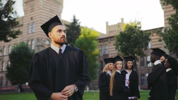 Portrait shot of the young graduated man in black traditional gown and cap standing in front of the camera with diploma and crossing his hands. Graduates on the background. Outdoors