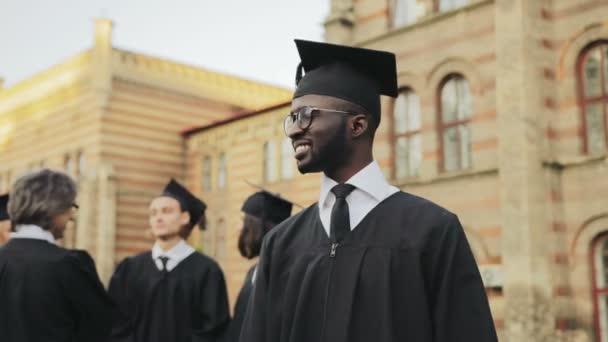 Az afrikai-amerikai boldog diplomás fiatalember pózol a kamerába, és bemutatja a diplomáját, az Egyetem előtt portréja. Diplomások professzor, a háttérben. A szabadban