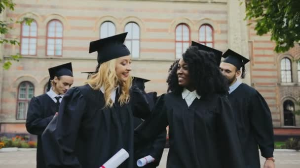 Happy smiled mixed races graduates walking with the diplomas in hands near the University building after the graduation ceremony. Outdoor