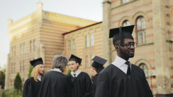 Portrait of the African American happy male graduate posing to the camera and smiling sincerely in front of the University. Graduates with professor on the background. Outside