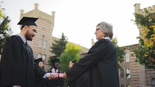 Šedá vlasy profesor gratulací pohledný muž absolvent a podal mu diplom před univerzitou. Další absolventi na pozadí. Vně