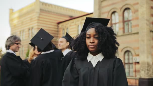 Portrait of the African American smiled young graduated woman posing to the camera and smiling in front of the University. Graduates with professor on the background. Outside