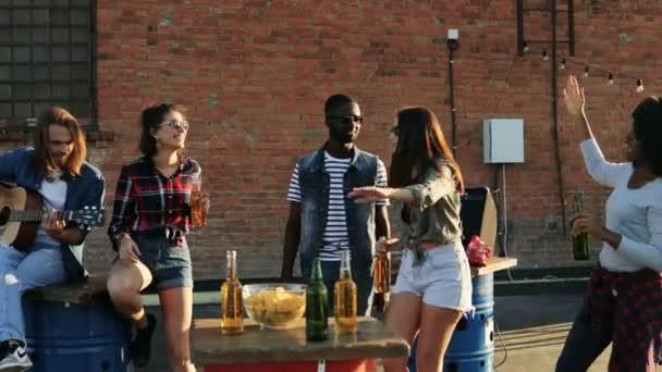 Skupina mladých lidí s kytarou a pivo na střeše stranou na cihlovou zeď na pozadí. Venkovní. Smíšené rasy