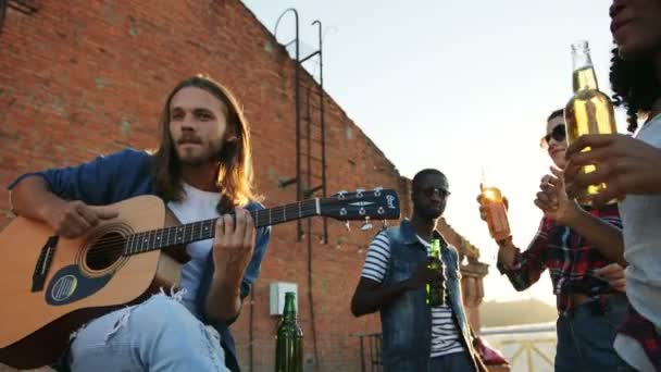 Mladí přátelé párty s kytarou na střeše stranou a říká hurá s pivem. Cihlová zeď pozadí. Venkovní. Smíšené rasy