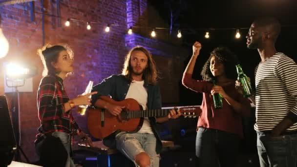 Skupina mladých lidí, párty a tanec, zatímco mladý muž s dlouhými vlasy, hrál na kytaru na střeše stranou. V noci. Cihlová zeď barvou světla. Venkovní. Mnohonárodnostní