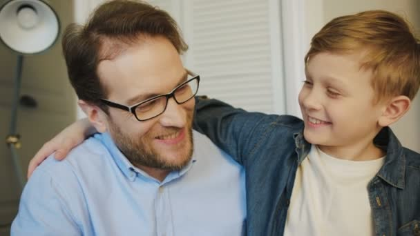 Portrait of the father in glasses and blonde young son looking at each other with smiles and then straight to the camera. Close up. Indoors.