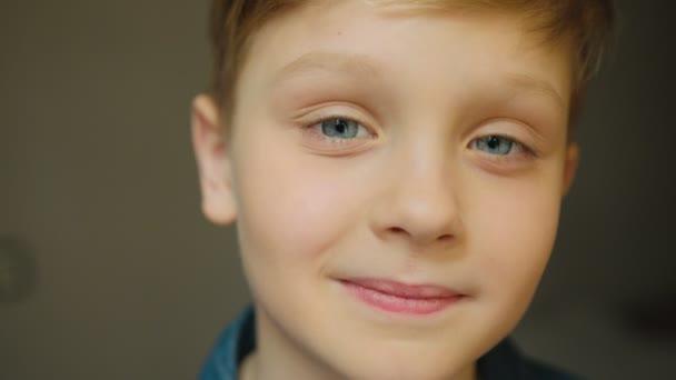 Zblízka se z krásné školák s modrýma očima vzhlédl při myšlení a pak se radostně k fotoaparátu. Portrét. Uvnitř