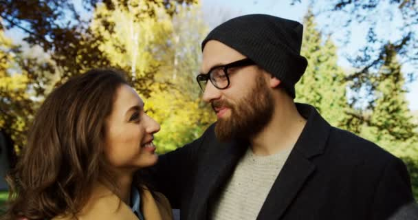 Portrait of young romantic attractive couple in love looking at each other and than smiling into the camera in beautiful park. Autumn sunny day. Close up. Outdoor